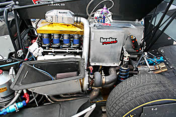 With the bodywork removed you can see half of the Chevy engine along with the Banks Sidewinder turbo. But also notice the rear suspension as well as the massive Continental tire that Dallenbach is able to spin at will with pressure from his right foot.